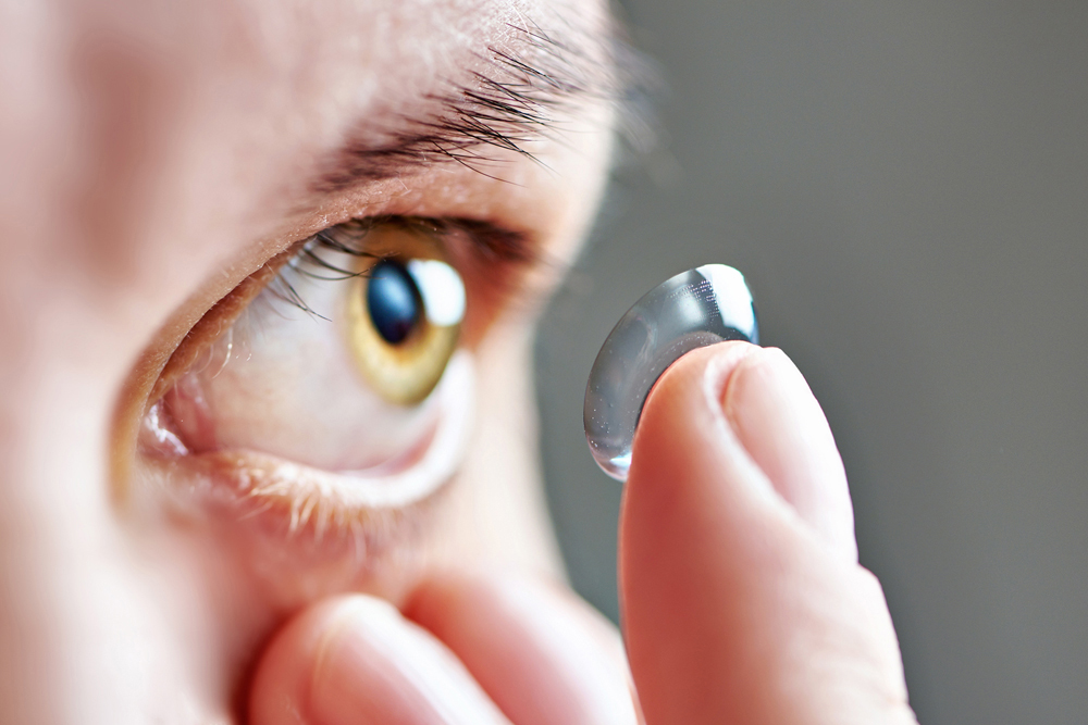 person putting in contacts for astigmatism